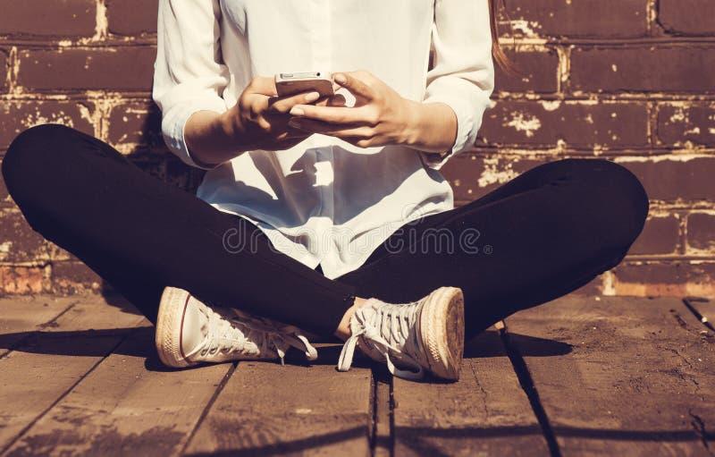 使用巧妙的电话的美丽的年轻行家妇女 免版税图库摄影