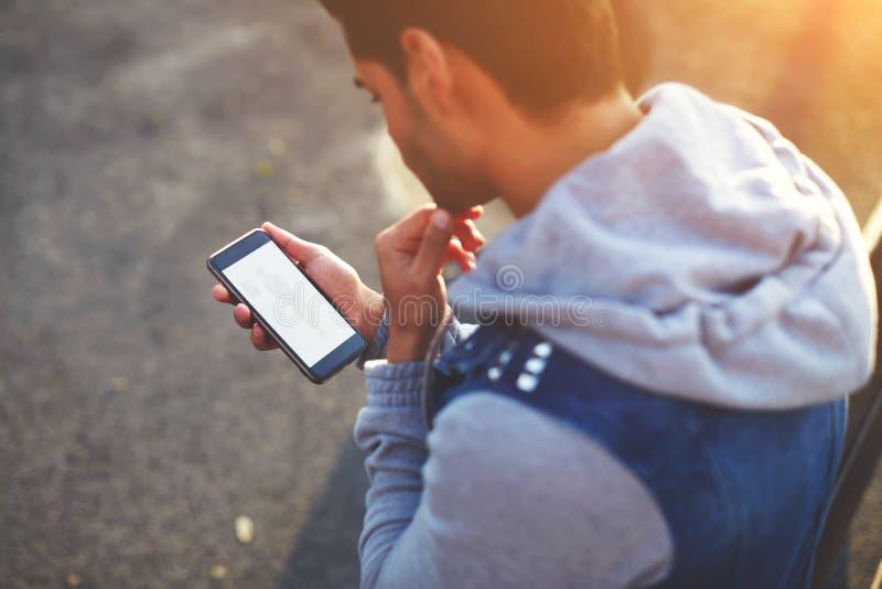 使用巧妙的电话的英俊的年轻人,当站立户外在晴朗的晚上时 免版税库存图片