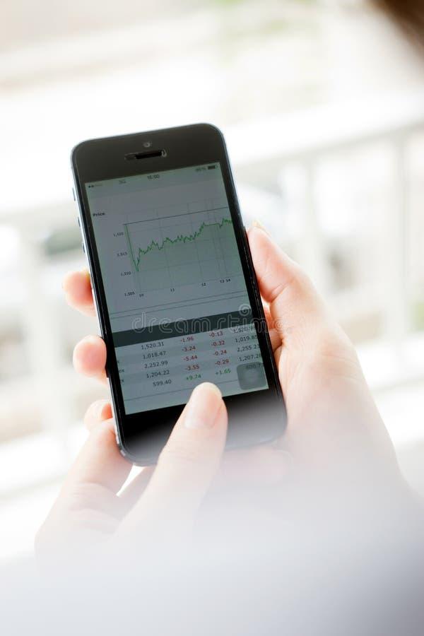 使用巧妙的电话,妇女分析股市 免版税库存照片