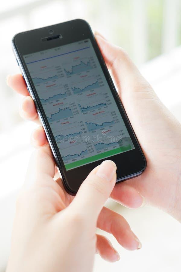 使用巧妙的电话,妇女分析股市 库存图片