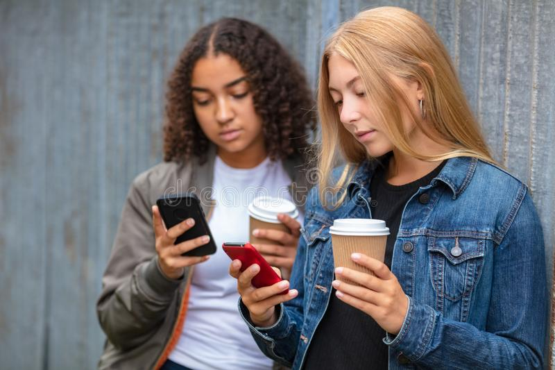 使用巧妙的电话Drinkin的人种间混合的族种女孩少年 免版税库存图片