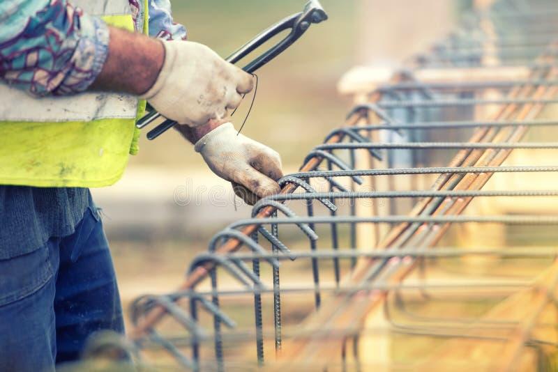 使用巩固钢绳和的钳子的工作者手在建造场所的酒吧 免版税库存照片