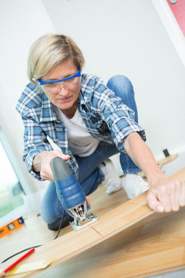 使用带锯的年轻女性木匠在车间 免版税库存照片