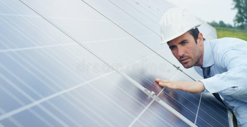 使用干净,关于太阳能光致电压的盘区的工程师专家与遥控进行系统监控的定期行动 免版税库存照片