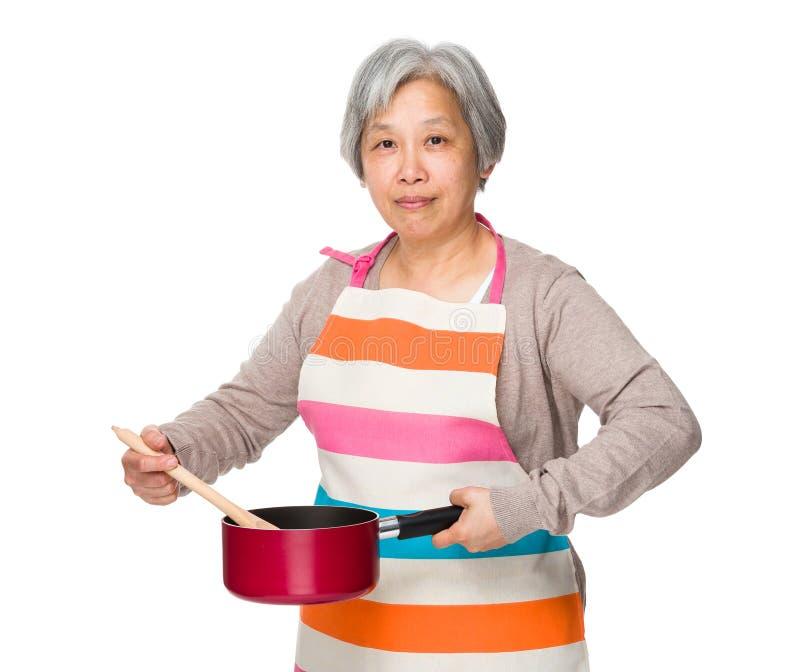 使用平底深锅和木杓子的年长主妇 免版税库存图片