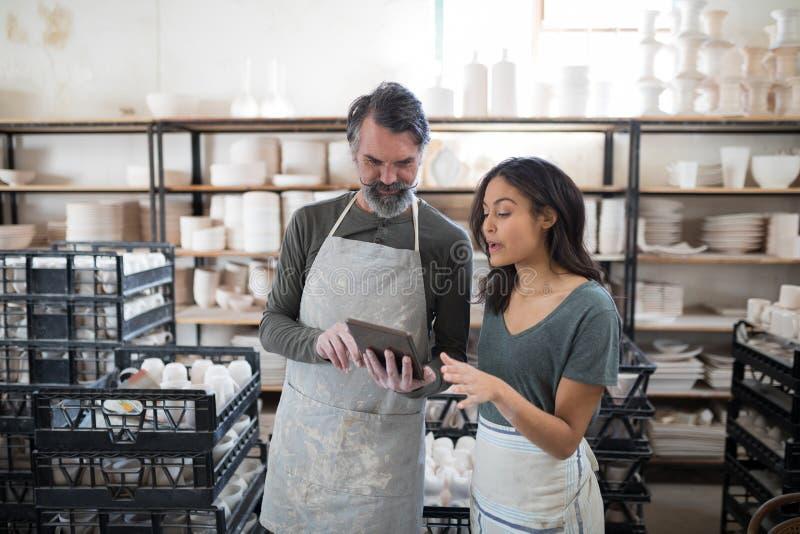 使用平板电脑和谈话的微笑的陶瓷工同事 免版税库存图片