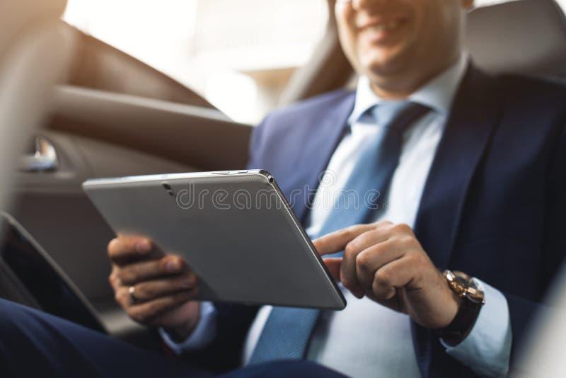 使用平板电脑的年轻商人,当坐汽车的后座时 白种人公商业主管乘出租汽车和 免版税库存图片