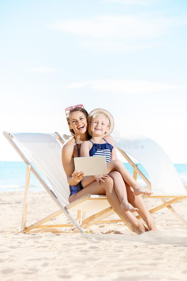 使用平板电脑的母亲和孩子,当坐海滩睡椅时 库存照片