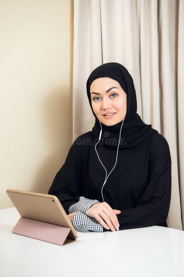 使用平板电脑计算机的阿拉伯妇女 东南亚学生在家 回教十几岁的女孩生存生活方式 免版税库存照片