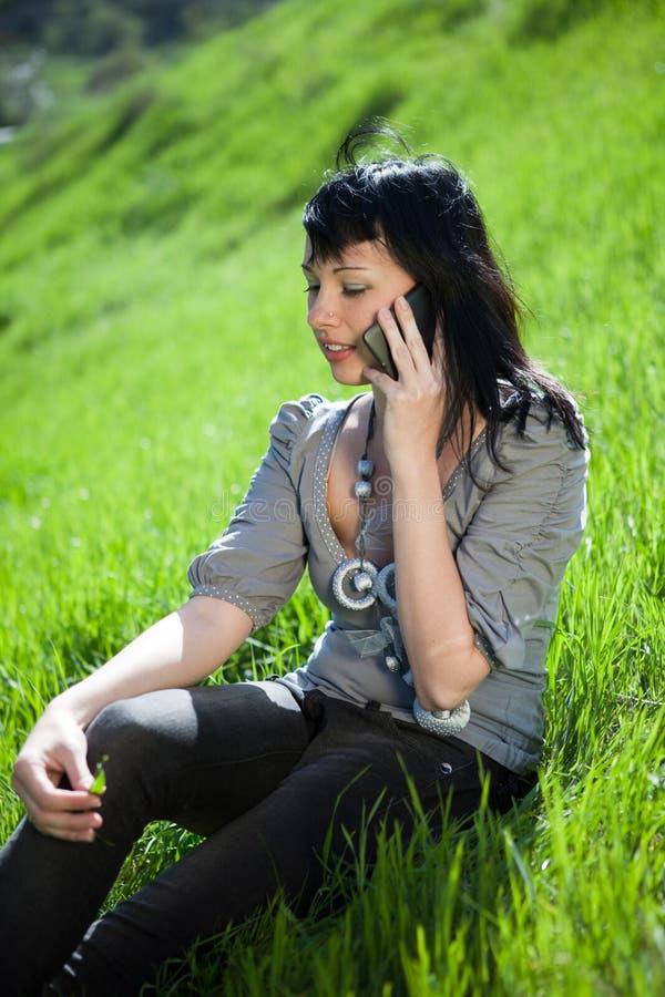 使用年轻人的电池女孩室外电话 免版税图库摄影