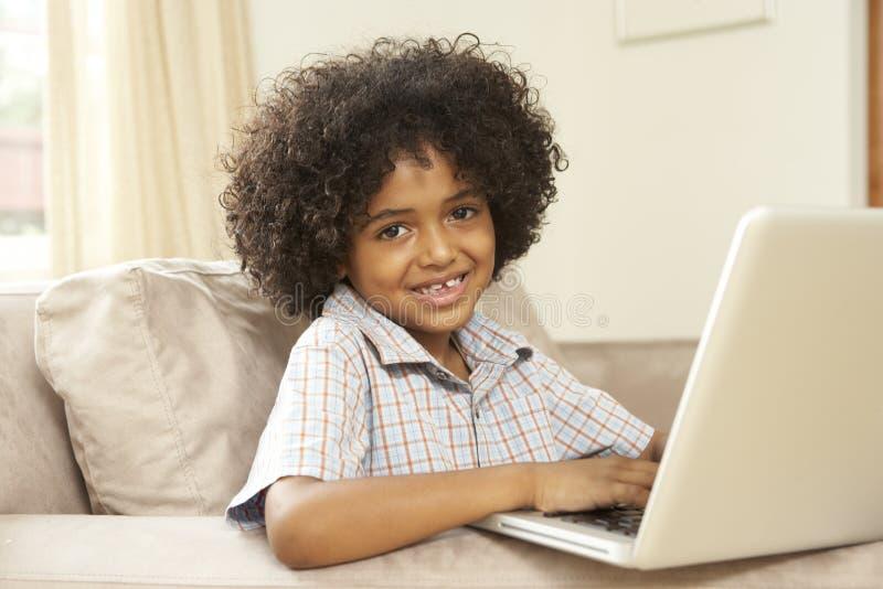 使用年轻人的男孩家庭膝上型计算机 库存图片