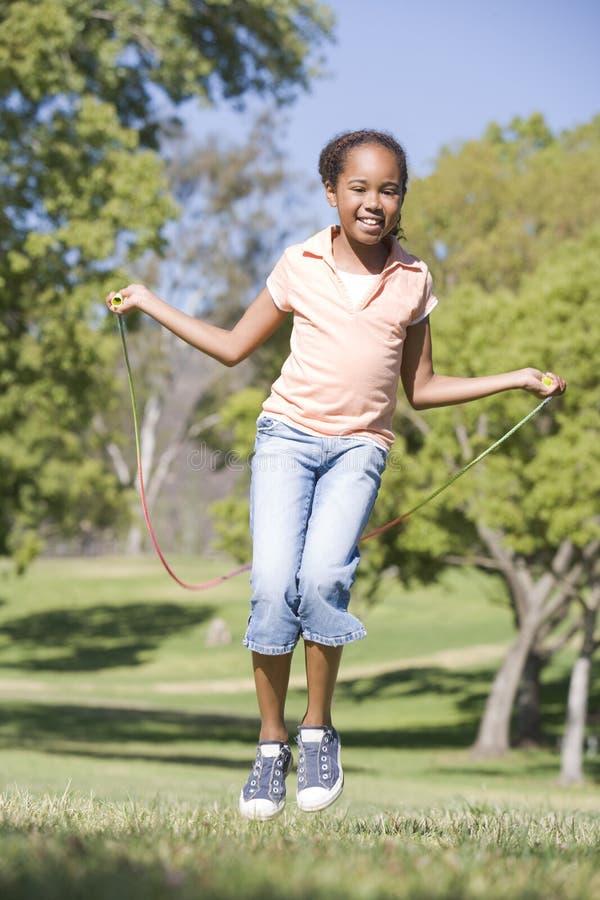 使用年轻人,户外女孩系住跳过的微笑 免版税库存图片