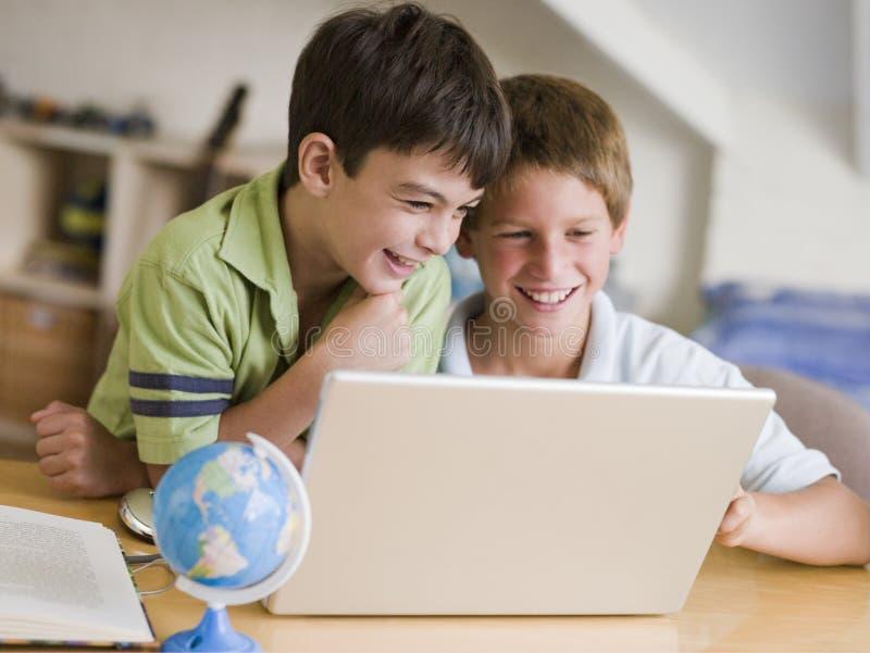 使用年轻人,男孩回家膝上型计算机二 免版税图库摄影