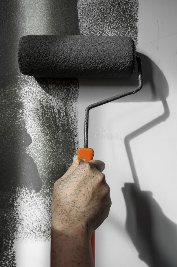 使用应用在白色墙壁上的路辗油漆的手灰色油漆 免版税库存图片