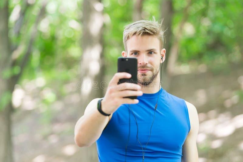 使用应用,创造路线奔跑 有智能手机的运动员和巧妙的手表为凹凸部做准备 与体育的训练 库存图片