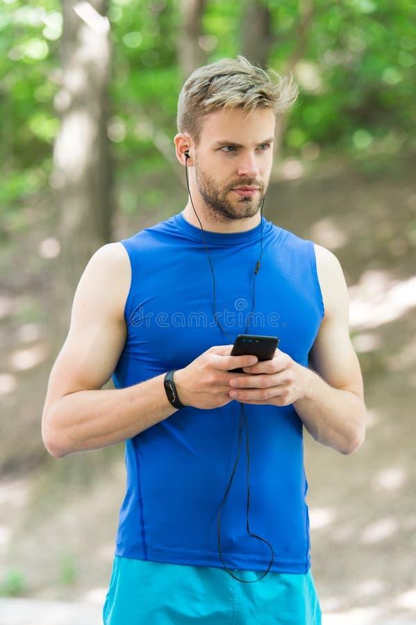 使用应用,设定奔跑的路线 准备好人的智能手机开始凹凸部 设定应用 有智能手机的运动员 库存照片
