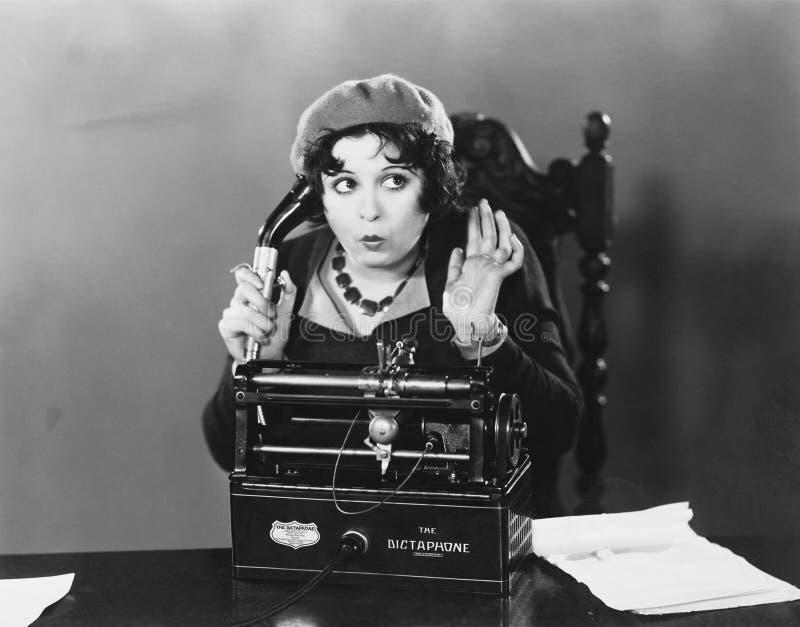 使用录音电话机的妇女 免版税库存照片
