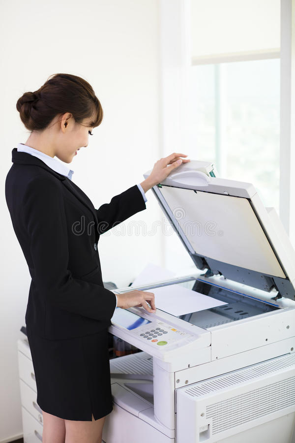 使用影印机的年轻女实业家 免版税库存照片