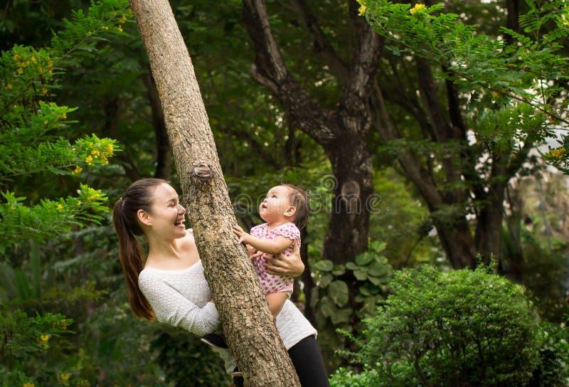 使用快乐在一棵树附近的愉快的母亲和女儿/婴孩在森林里 图库摄影
