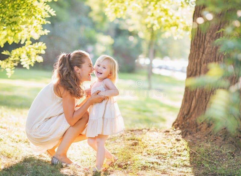 使用愉快的母亲和的婴孩画象户外 免版税库存照片