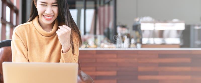 使用或看手提电脑的年轻可爱的亚裔学生微笑与成功在咖啡馆咖啡馆 亚洲妇女或愉快 免版税库存照片
