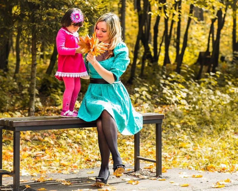 使用户外与秋季槭树叶子的女孩和她的母亲 采摘金黄叶子的女婴 库存图片