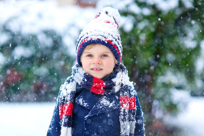 使用户外在强的降雪期间的五颜六色的衣裳的滑稽的小孩男孩 库存图片