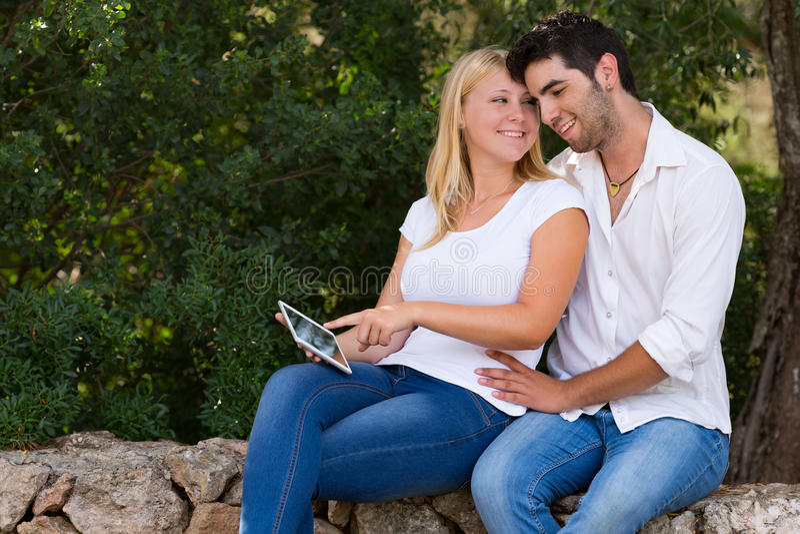 使用户外数字式片剂的少年夫妇 图库摄影