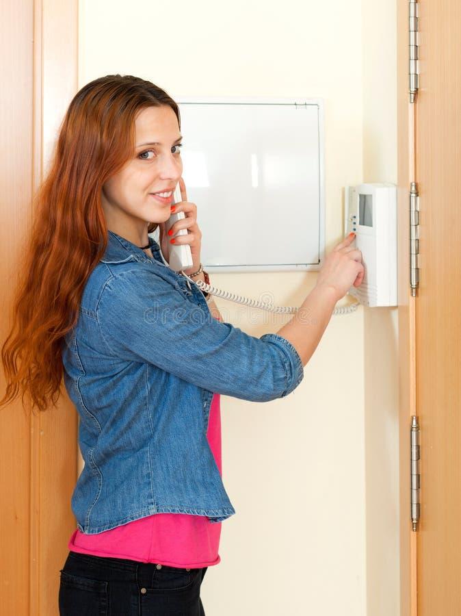 使用房子可视电话的年轻美丽的妇女室内 库存图片