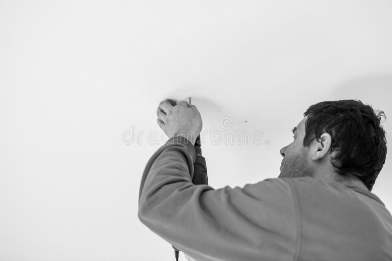 使用手扶的电钻的工作员的灰度的图象 图库摄影
