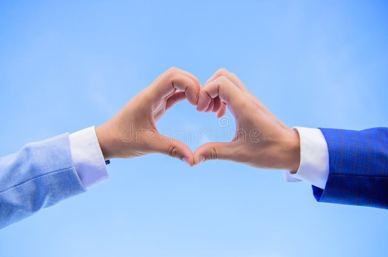 使用手指,手心脏姿态形成形状 在心脏形状的男性手打手势爱和浪漫史的标志 背景爱红色玫瑰色符号白色 库存照片