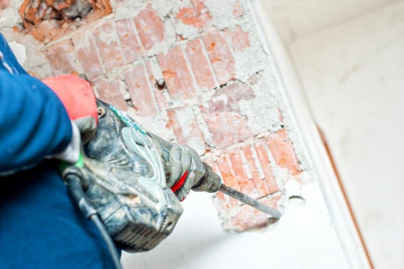 使用手提凿岩机的杂物工对distroy混凝土墙 库存照片