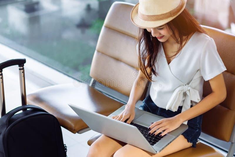 使用手提电脑机场的妇女少年 免版税库存照片