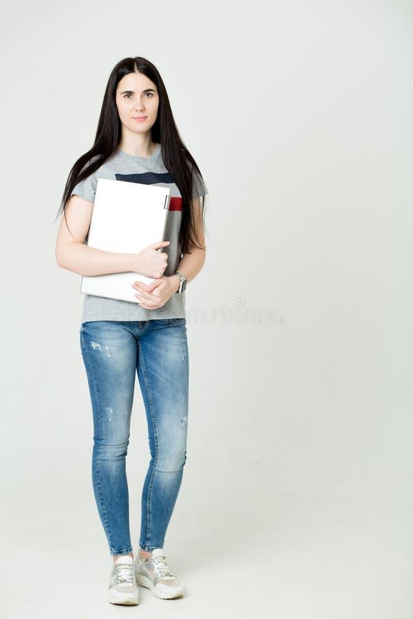 使用手提电脑的一名愉快的妇女的全长画象隔绝在白色背景 免版税库存照片