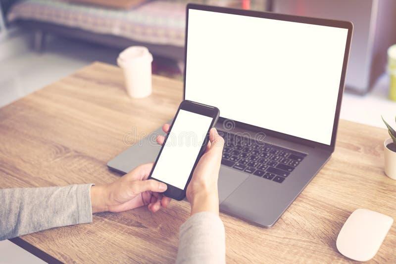 使用手提电脑的女商人做在木桌上的网上活动和举行电话 库存图片