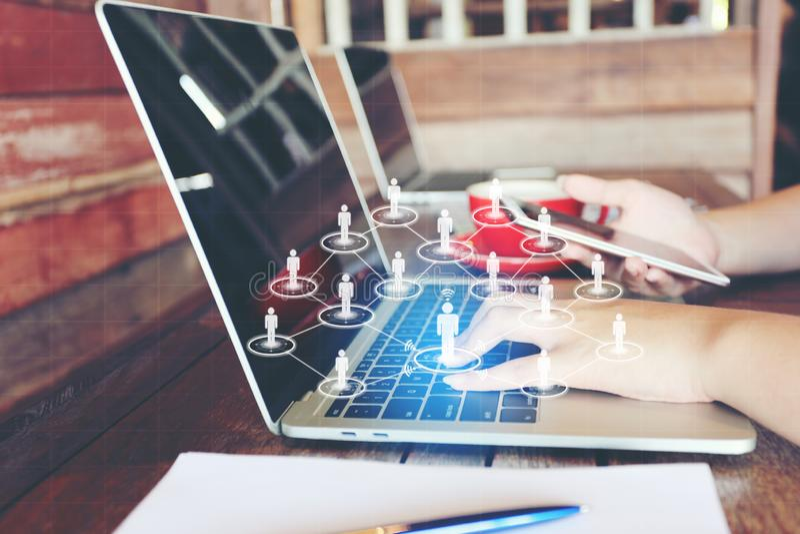 使用手提电脑的年轻女人和象或者全息图在咖啡馆、社会媒介通讯网络互联网和事务 免版税库存照片