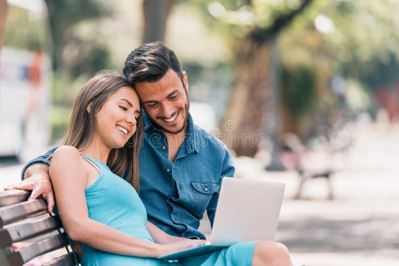使用手提电脑的愉快的年轻夫妇坐一条长凳在室外的城市-获得两个的恋人一起花费时间的乐趣 库存图片