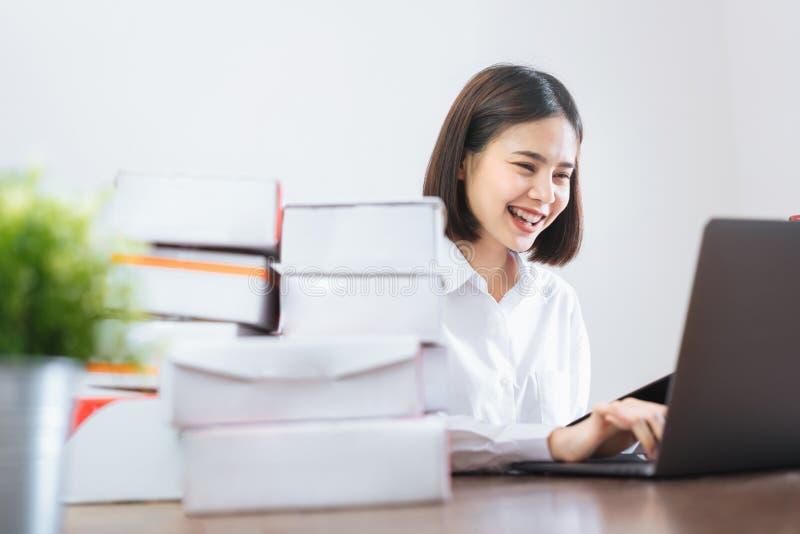 使用手提电脑的愉快的微笑的亚裔妇女检查单顾客和网上交货为准备好包装 免版税库存照片