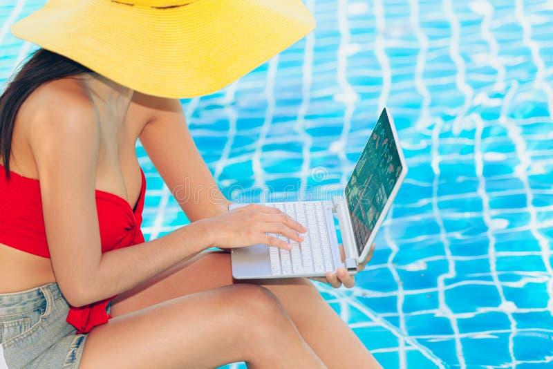 使用手提电脑的逗人喜爱的青少年的亚裔妇女喜欢工作在游泳场 免版税库存图片