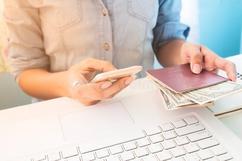 使用手机和举行passpor的妇女佩带的牛仔裤衬衣 免版税库存图片