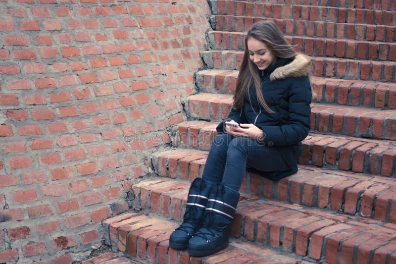 使用手机和微笑的美丽的十几岁的女孩 库存图片