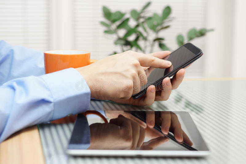 使用手机和数字式片剂的商人 免版税库存图片