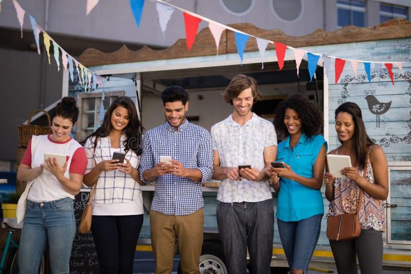 使用手机和数字片剂的朋友在柜台 免版税库存图片