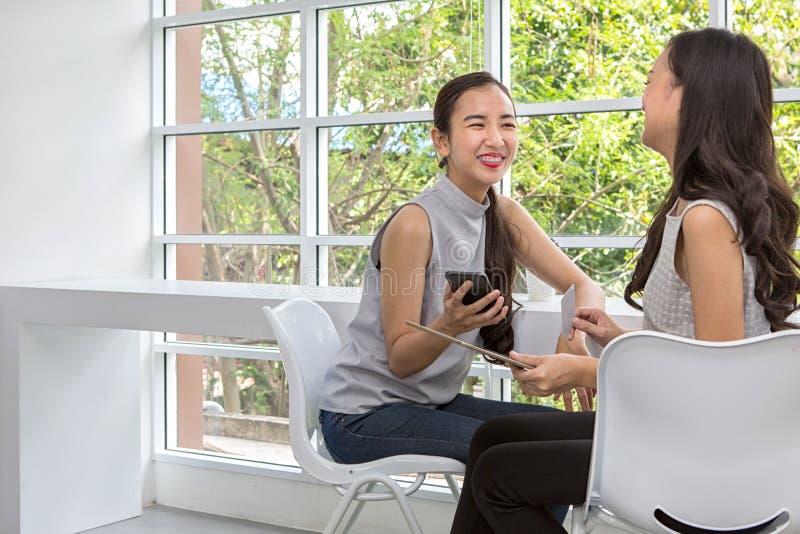 使用手机和片剂的两名愉快的妇女坐在咖啡店 微笑使用片剂的两个少妇最好的朋友 女性 库存图片
