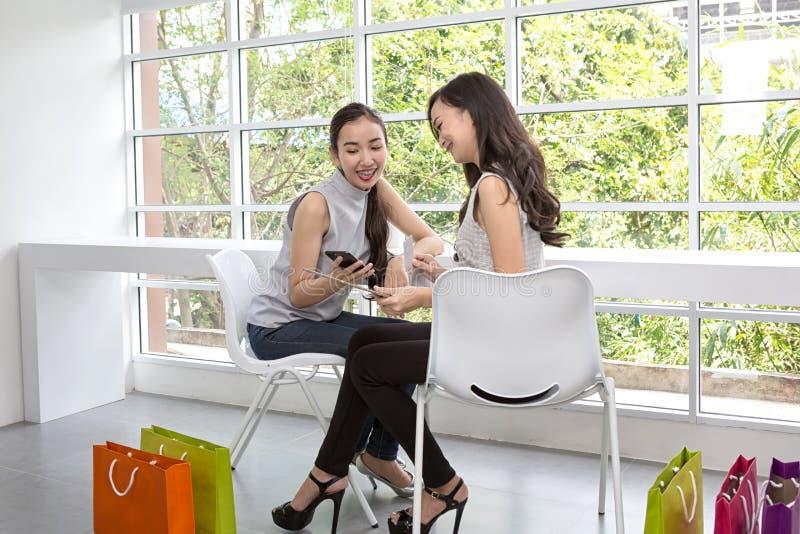 使用手机和片剂的两名愉快的妇女坐在咖啡馆 微笑使用片剂的两个年轻女人最好的朋友 ?? 库存图片