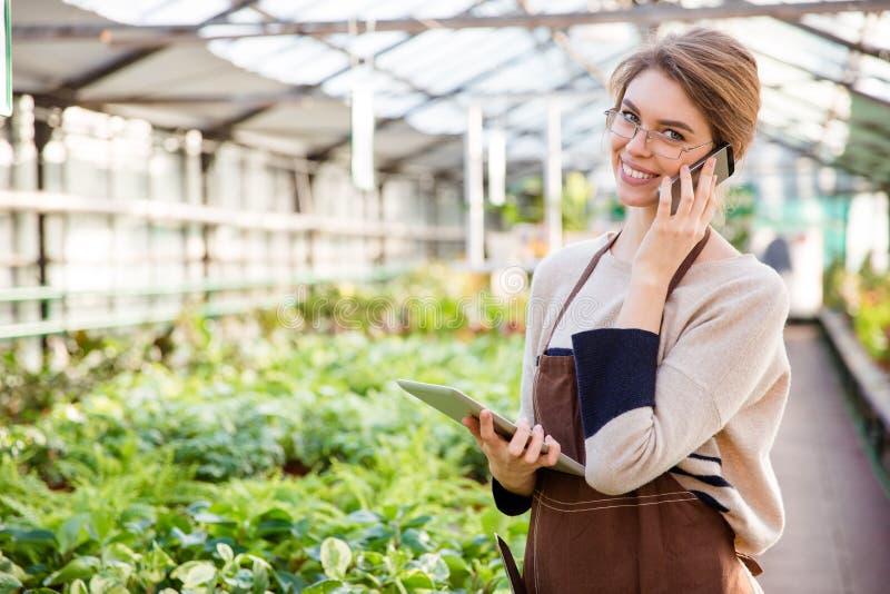 使用手机和片剂的微笑的妇女花匠在温室 免版税库存图片