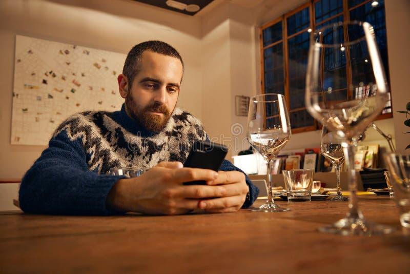 使用手机在餐馆 免版税图库摄影