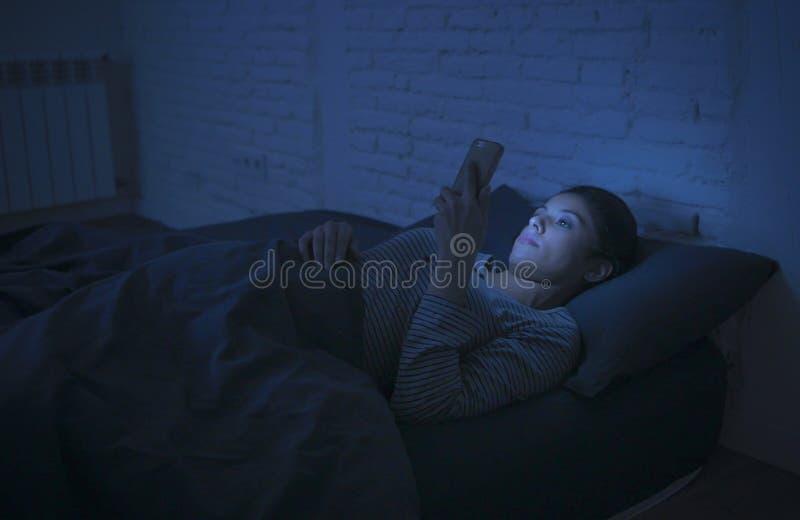使用手机夜间失眠说谎的年轻美丽的拉丁妇女画象在黑暗的床在智能手机和实习生 库存照片