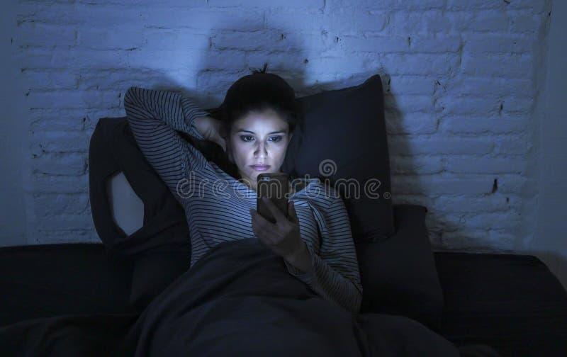 使用手机夜间失眠说谎的年轻美丽的拉丁妇女画象在黑暗的床在智能手机和实习生 免版税库存照片