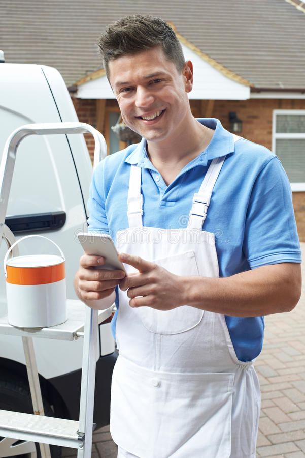 使用手机常设外部国内家的装饰员 免版税库存照片